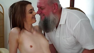 Teen cutie is stroking and sucking old guy on the massage table